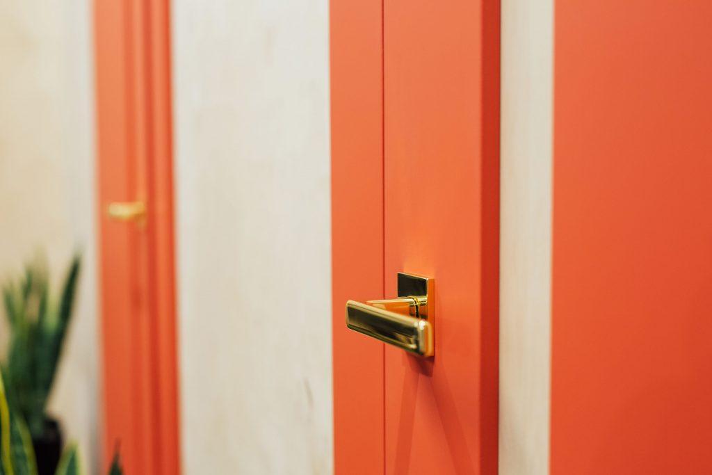 Drzwi LUKKA marki INTER DOOR - w koralowej okleinie, ze sklejką zamiast przeszklenia i złotymi okuciami